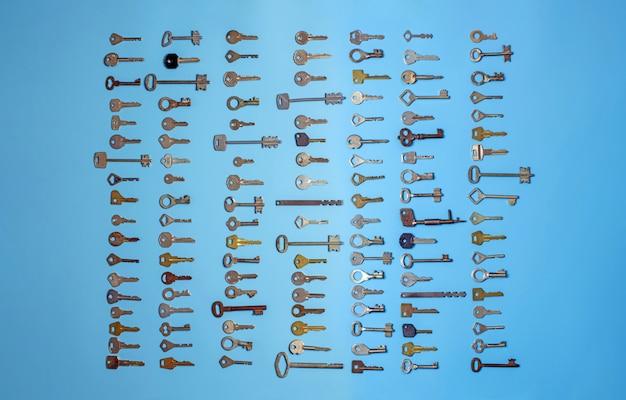 Klucze ustawione na niebieskim tle, klucze do zamków i sejfy do zabezpieczenia mienia