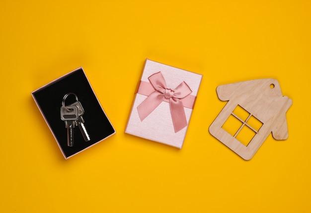 Klucze w ozdobnym pudełku z kokardką, figurka domku na żółtym tle. obudowa na prezent. widok z góry