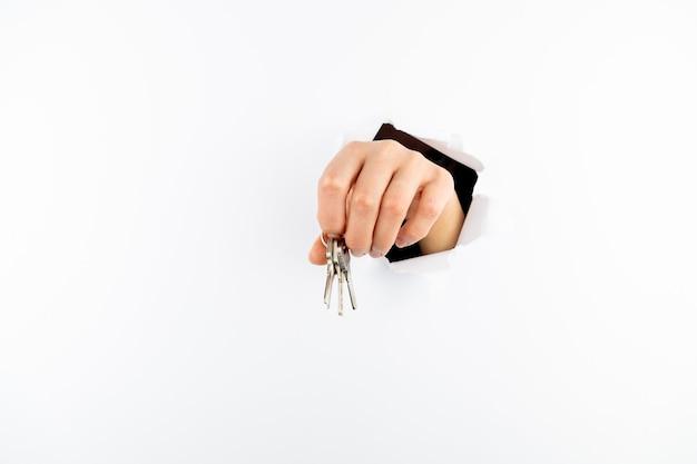 Klucze w ręku. ręka przebija białą ścianę i pokazuje klucze przez otwór.