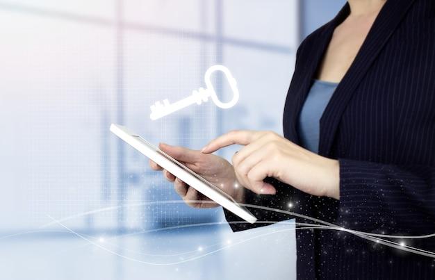 Kluczowa ikona słowa kluczowego business internet technology concept. ręka dotykowy biały tablet z cyfrowym hologramem klucz znak na jasnym tle niewyraźne. koncepcja bezpieczeństwa i ochrony.