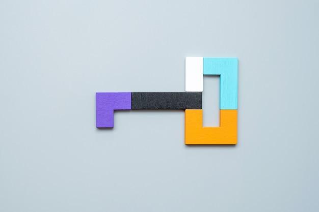 Kluczowy kształt geometrycznych kolorowych drewnianych puzzli.