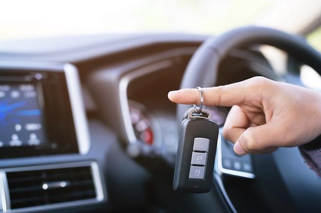 Kluczyk, biznesmen przekazanie daje kluczyk drugiemu człowiekowi na tle samochodu.