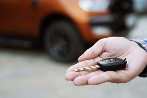 Kluczyk, przekazanie biznesmena daje kluczyk drugiemu człowiekowi na samochodzie b