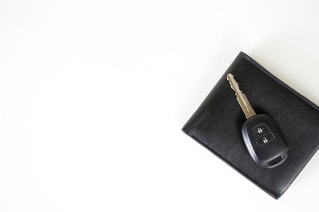 Kluczyki do samochodu na portfelu na białym tle z miejscem po lewej stronie.
