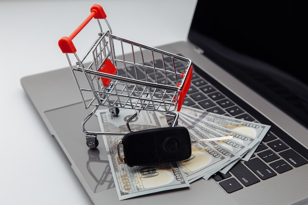 Kluczyki do samochodu z banknotami dolara i koszyk na klawiaturze. koncepcja samochodu zakupu online.