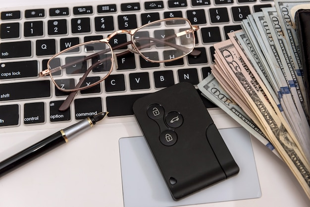 Kluczyki do samochodu z rachunkami dolarowymi na klawiaturze laptopa, koncepcja sprzedaży