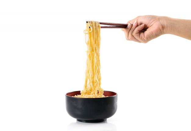 Kluski chopsticks w czarnym pucharze na białym tle