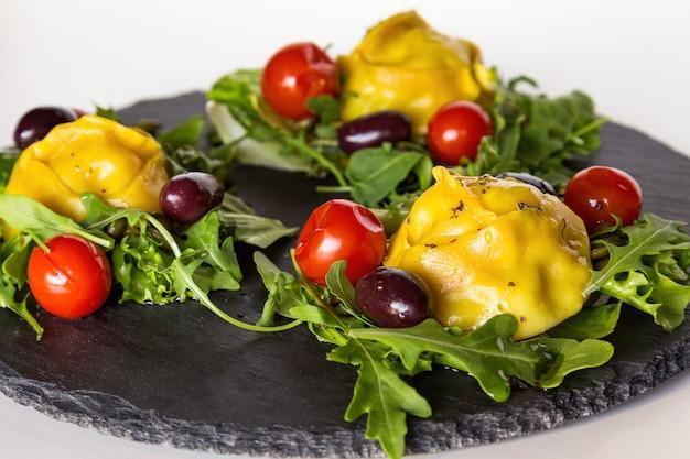Kluski mięsne na parze manti z warzywami i zieleniną na czarnym kamiennym talerzu.
