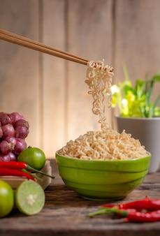 Kluski w bowlwith wapno, chili, cebula i warzywo na drewnianym stole
