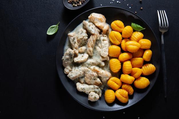 Kluski z batatów z kurczakiem w sosie podawane na ciemnym talerzu.