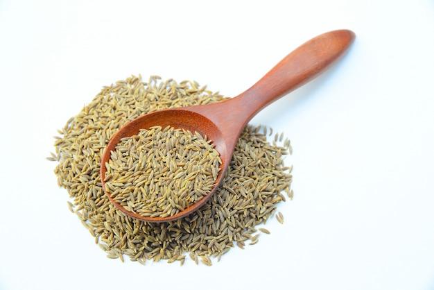Kminku lub kminku ziarna w drewnianej łyżce na białym tle