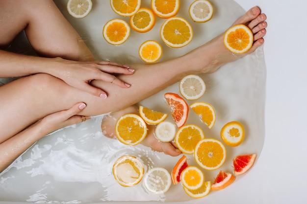 Kobieca dłoń i nogi w wannie wypełnionej wodą i różnymi pokrojonymi owocami cytrusowymi