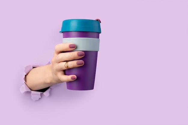 Kobieca dłoń przez dziurę w papierze trzyma kubek wielokrotnego użytku. życie przyjazne dla środowiska. koncepcja zero waste. na wynos wypij kawę herbatę na wynos