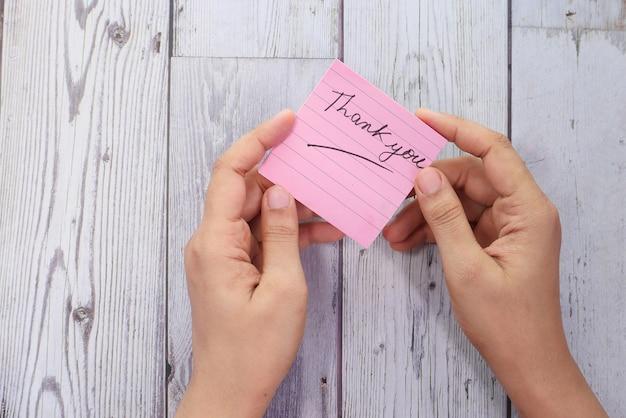 Kobieca dłoń trzymająca notatkę z podziękowaniami, z góry na dół.