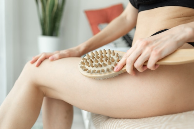 Kobieca dłoń trzymająca suchy pędzel w górnej części nogi. zabieg na cellulit, oczyszczanie skóry suchej.