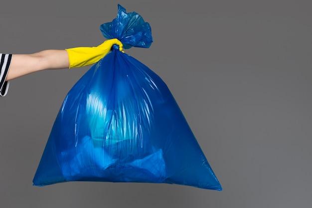 Kobieca dłoń w gumowej rękawicy trzyma niebieską plastikową torbę pełną śmieci.