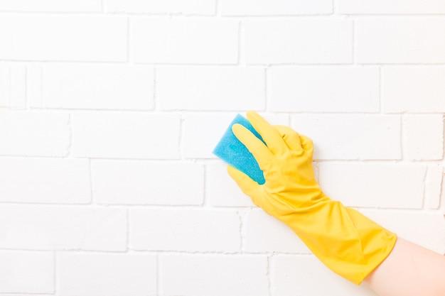 Kobieca dłoń w gumowej rękawiczce trzyma niebieską gąbkę paralonową do czyszczenia i zmywania naczyń