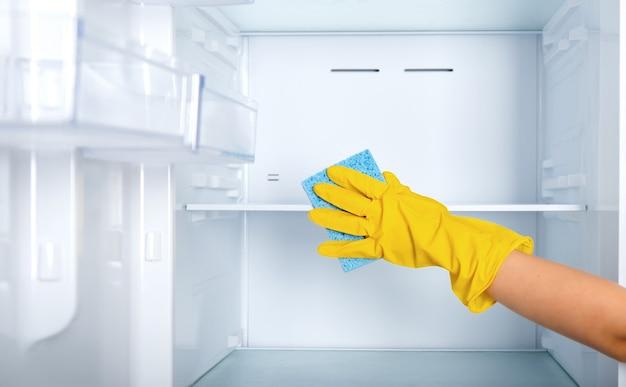 Kobieca dłoń w żółtej gumowej rękawicy ochronnej i niebieskiej gąbce myje i czyści półki lodówki.
