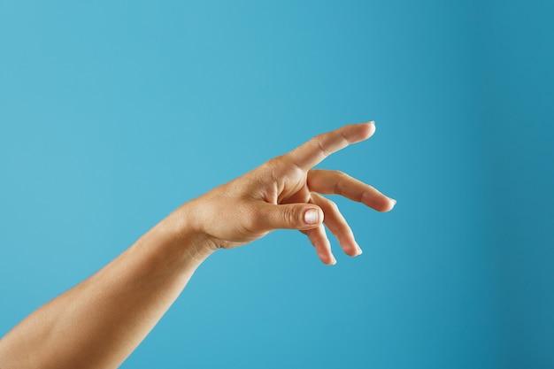 Kobieca dłoń wymagająca wsparcia i pomocy rozciąga się na niebieskim tle