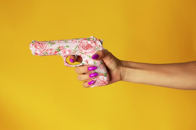 Kobieca dłoń z fioletowymi paznokciami trzyma w dłoni różowy pistolet pomalowany różami