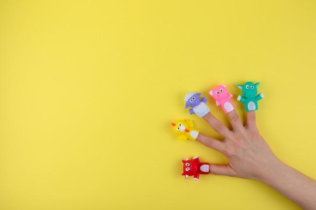 Kobieca dłoń z lalkami z 5 palcami: krowa, owca, kurczak, świnia. pojęcie rozwoju dziecka. miejsce do skopiowania. leżał na płasko.