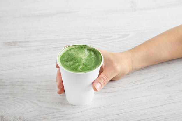Kobieca dłoń zabiera papierowe szkło z przygotowaną japońską organiczną matcha latte premium. na białym drewnianym stole.
