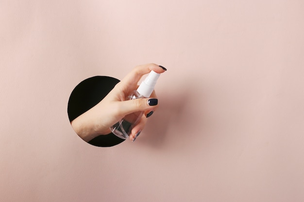 Kobieca dłoń ze środkiem antyseptycznym na dłoń przez okrągły otwór w różowym papierze