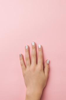 Kobieca dłoń ze stylowym lekkim makijażem na różowej powierzchni