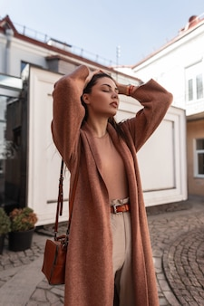 Kobieca elegancka piękna młoda kobieta w modnym płaszczu z brązową skórzaną torebką pozuje w pobliżu białego budynku na ulicy. sexy dziewczyna modelka prostuje szykowne długie włosy. piękna pani na zewnątrz.