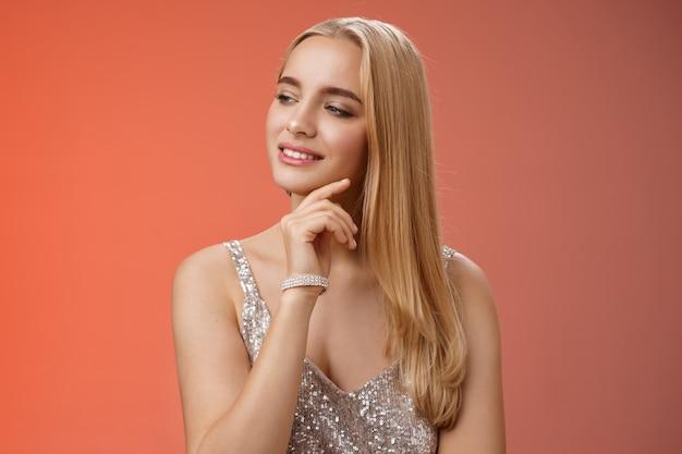 Kobieca elegancka zamożna kobieta bierze udział w luksusowej imprezie, czule dotykając policzka, ubrana w drogie modne, błyszczące akcesoria w srebrnej błyszczącej sukience, stojącej na czerwonym tle pewnie.