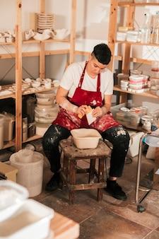 Kobieca garncarka wycierająca małe płytki gąbką w warsztacie