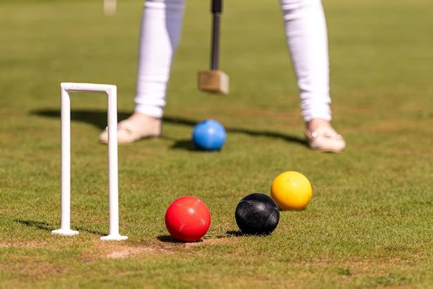 Kobieca gra w krokieta uderzająca piłkę młotkiem