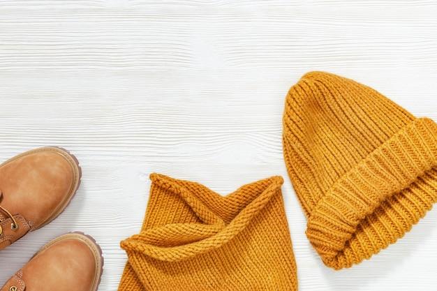 Kobieca jasnopomarańczowa odzież, ciepły szal z dzianiny wełnianej, czapka i przytulne buty. zakupy przeglądu koncepcji z miejsca kopiowania. koncepcja mody. widok z góry. leżał płasko.