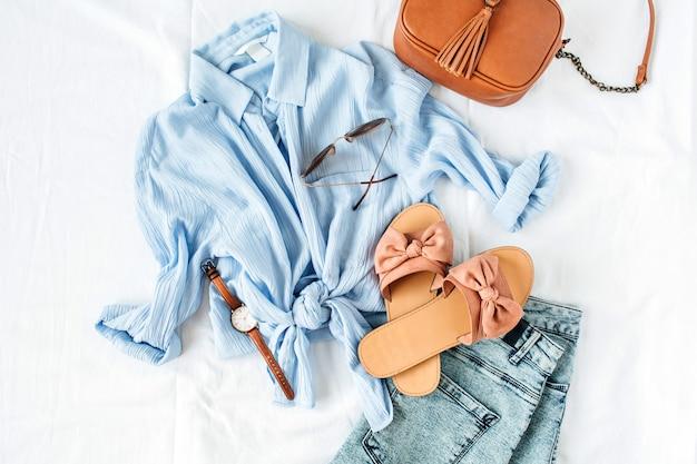 Kobieca kompozycja letniej mody z bluzką, kapciami, torebką, okularami przeciwsłonecznymi, zegarkiem i spodenkami na białej powierzchni