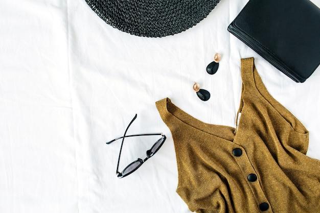 Kobieca kompozycja letniej mody z czapką, bluzką, kolczykami, torebką i okularami przeciwsłonecznymi na białej powierzchni