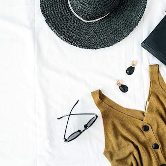 Kobieca kompozycja modowa z czapką, bluzką, kolczykami, torebką, okularami przeciwsłonecznymi na białym tle