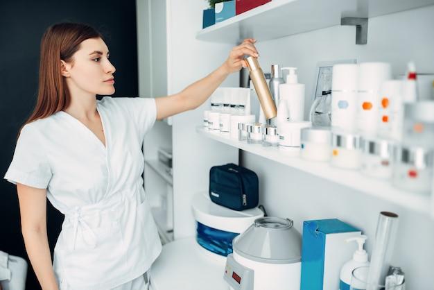 Kobieca kosmetyczka z butelką kremu w ręce