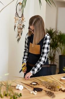 Kobieca kwiaciarnia robi piękny bukiet suszonych kwiatów i papieru rzemieślniczego na drewnianym stole