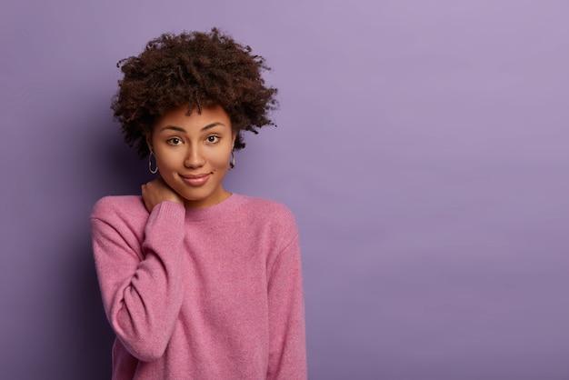 Kobieca modelka z kręconymi włosami dotyka szyi, ma delikatny wygląd, zachwycony uśmiech, spokojny wyraz twarzy, swobodną rozmowę z przyjaciółką, nosi sweter z długimi rękawami, pozuje na fioletowej ścianie, z boku puste miejsce.