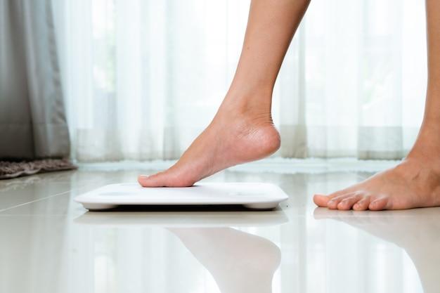 Kobieca noga stąpa po białych łuskach w domu