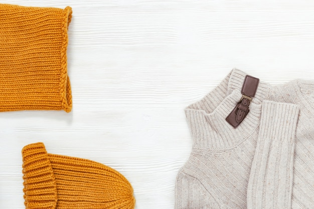 Kobieca odzież jesienna, ciepły szalik i czapka w kolorze pomarańczowym oraz jasny wełniany sweter. zakupy przeglądu koncepcji z miejsca kopiowania. widok z góry. leżał płasko.