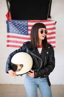Kobieca piękna kobieta lub nastolatka nosi nowe okulary przeciwsłoneczne przed amerykańską flagą, modny i modny hipster, patriota usa