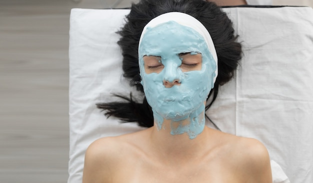 Kobieca pielęgnacja skóry zbliżenie pięknej dziewczyny z kosmetyczną maską na skórę twarzy w...
