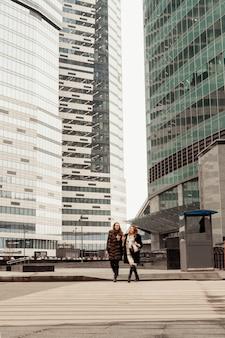 Kobieca przyjaźń, relacje. dwie dziewczyny piją kawę na ulicy w pobliżu szklanych biurowców, korporacji, banku. koniec dnia roboczego menedżera. kawa w biegu.