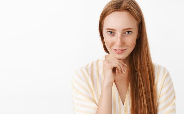 Kobieca, przystojna, zalotna ruda kobieta z piegami w ślicznej sukience z dekoltem w szpic, trzymająca dłoń na szczęce i uśmiechająca się zmysłowym uwodzicielskim spojrzeniem