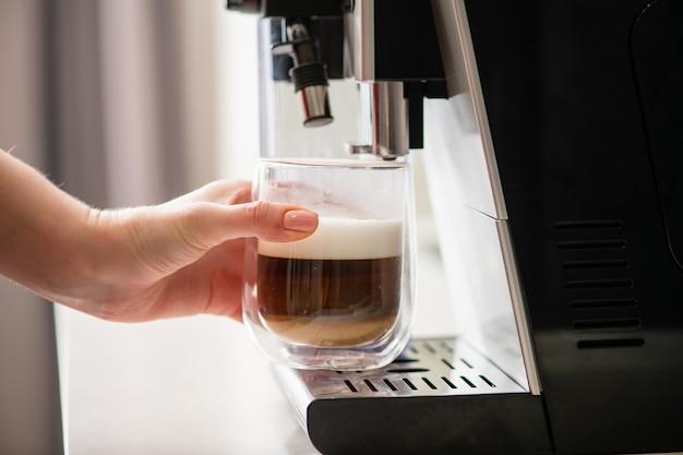 Kobieca ręka bierze szklankę z ekspresu do kawy