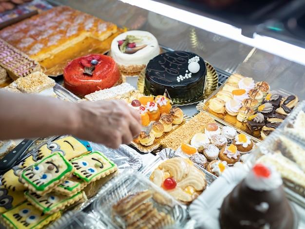 Kobieca ręka biorąca ciasto w cukierni