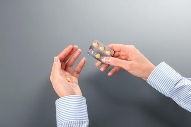 Kobieca ręka biorąca pigułkę. kobieta ma nieprawidłowe tętno. ten leczy alergię. zapamiętaj dawkowanie.