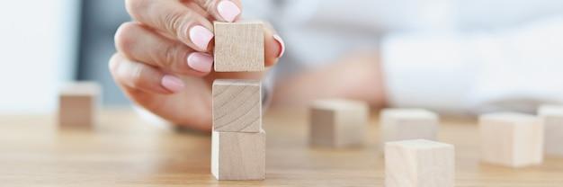 Kobieca ręka buduje wieżę z drewnianych kostek