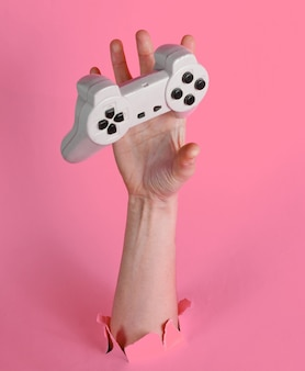 Kobieca ręka chwyta gamepad przez podarty różowy papier. minimalistyczna koncepcja kreatywna